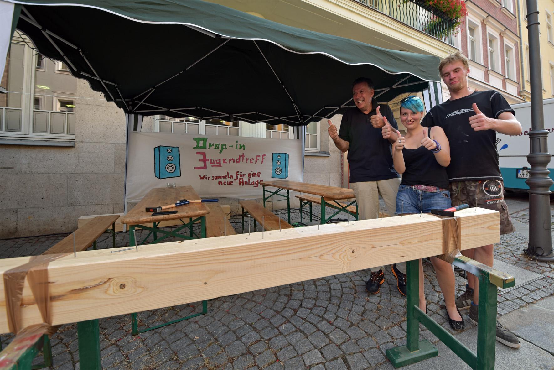 Reinhard Kreuz vom Lions Club Mittweida (links) freut sich mit Jessica und Nick vom drop in auf viele Besucher, die sich für die neue Musikanlage am Nagelbalken ins Zeug legen. Das Plakat haben die Jugendlichen selbst erstellt.